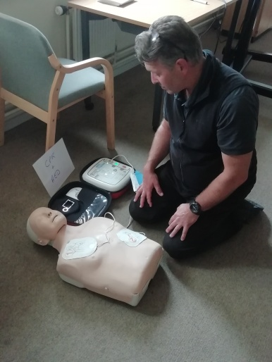 DaCE Training for PA's in Cumbria. Photograph of man taking part in a training course. He is practising CPR on a dummy.
