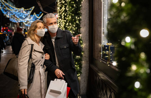Photograph of a man and women Christmas shopping. They are both wearing face masks.