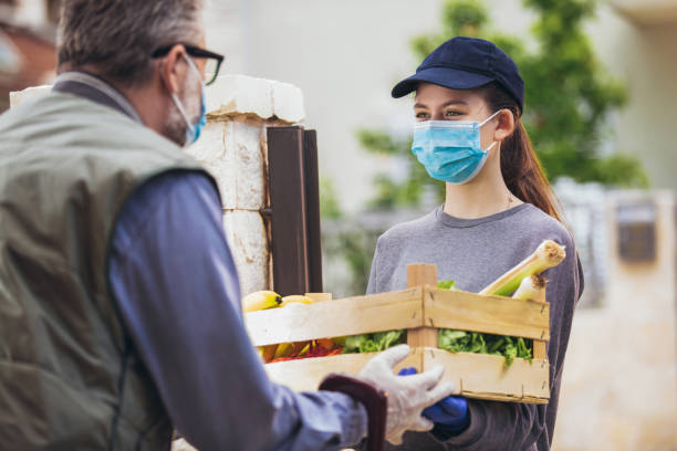 Phtograph of a women passing a box of fresh vegetables to a man. They are both wearing face masks.