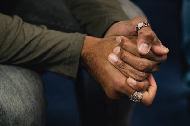 Photograph of a mans hands. the hands are clenched together.