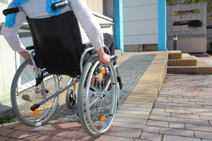 Photograph of a disabled person using a wheelchair to access a building via a ramp.